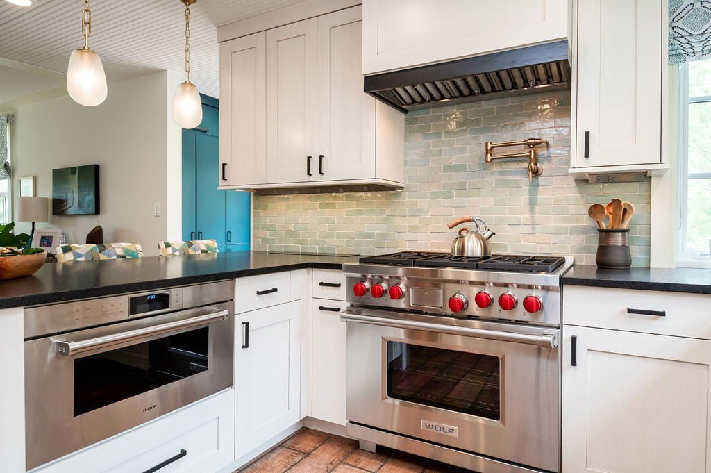 Kitchen with white custom cabinetry, dark marble countertops, white paneling on ceiling, stainless steel appliances, light green tile backsplash, and hanging lights (Zoomed out)
