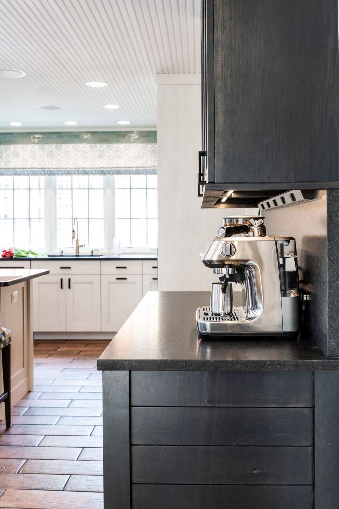 Dark hardwood cabinetry with dark marble countertops and stainless steel appliances