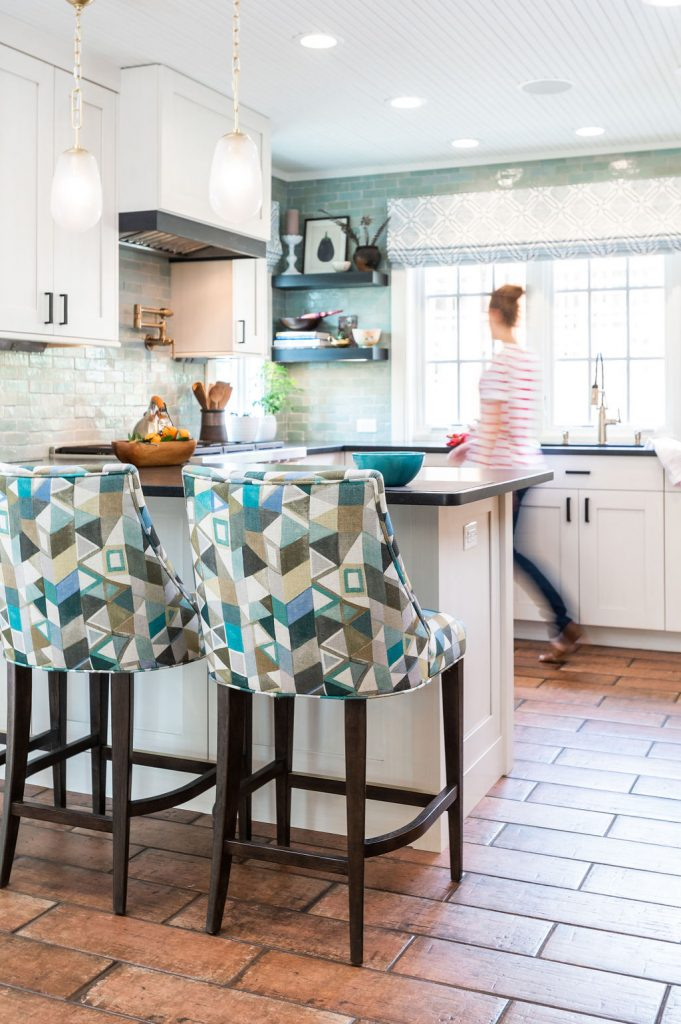 Transitional kitchen with custom white cabinetry, brown terra-cotta tile flooring, dark marble countertops, and blue-green accents on walls and hi-top chairs (With woman, different angle)