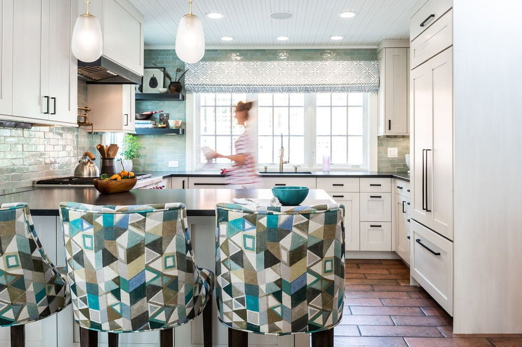 Transitional kitchen with custom white cabinetry, brown terra-cotta tile flooring, dark marble countertops, and blue-green accents on walls and hi-top chairs (With woman)