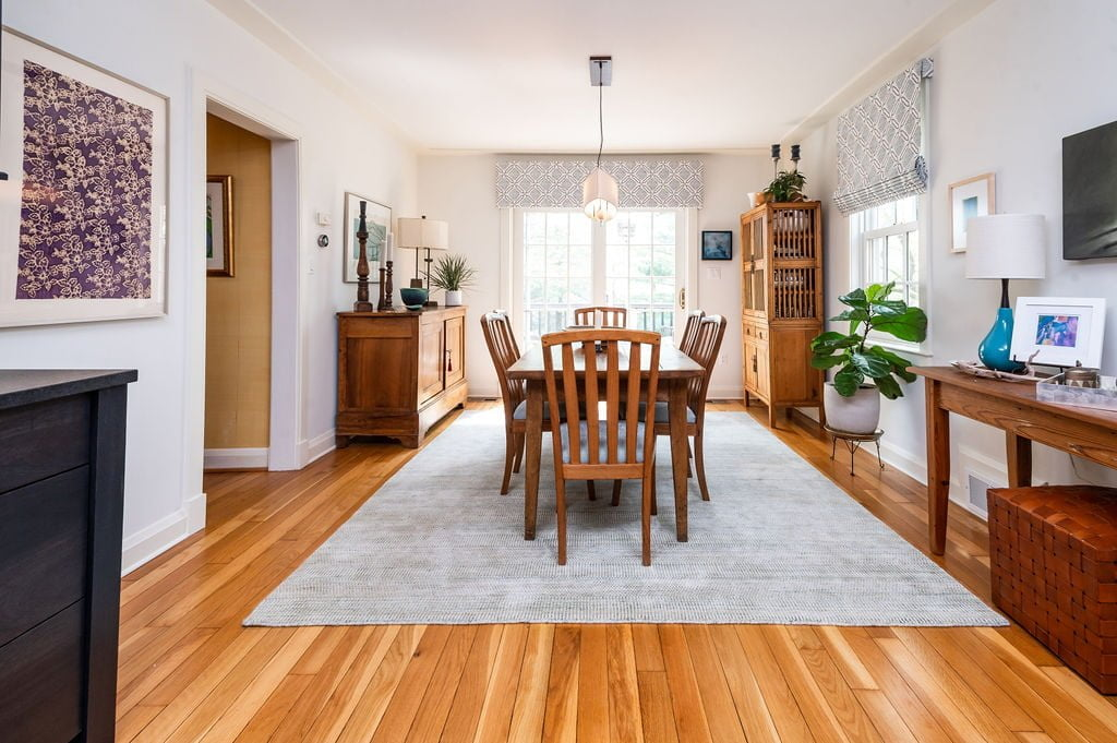 Traditional dining room with wooden table, chairs, flooring and cabinetry, with plain grey rug and white walls