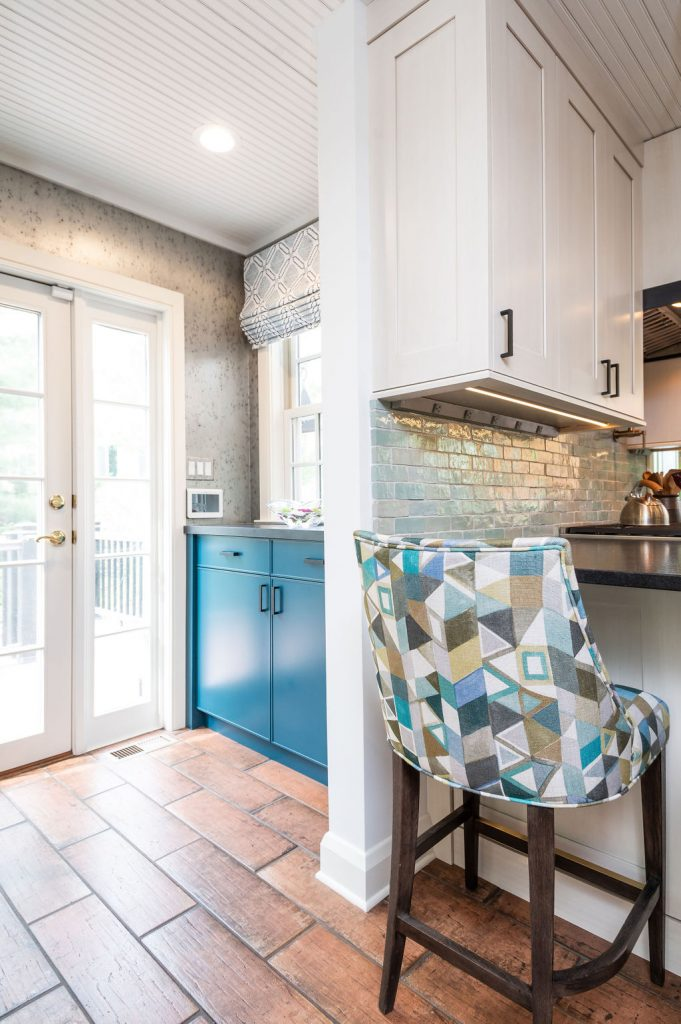 White door porch exit with transitional blue cabinetry, grey speckled walls, and brown terra-cotta tile flooring (Zoomed out)