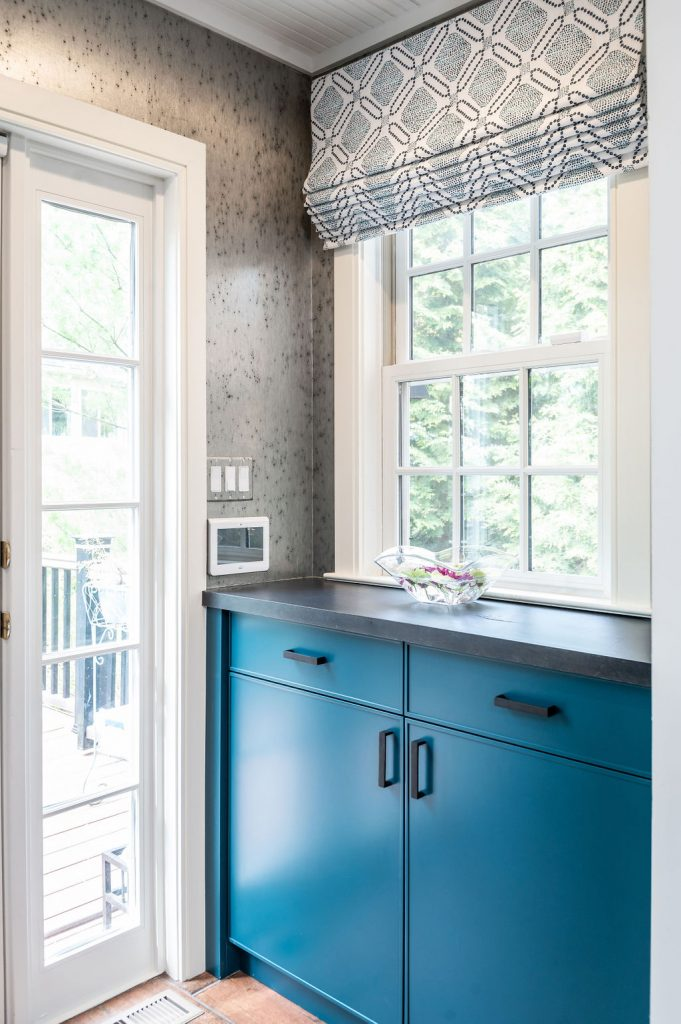 White door porch exit with transitional blue cabinetry and grey speckled walls (Different view)