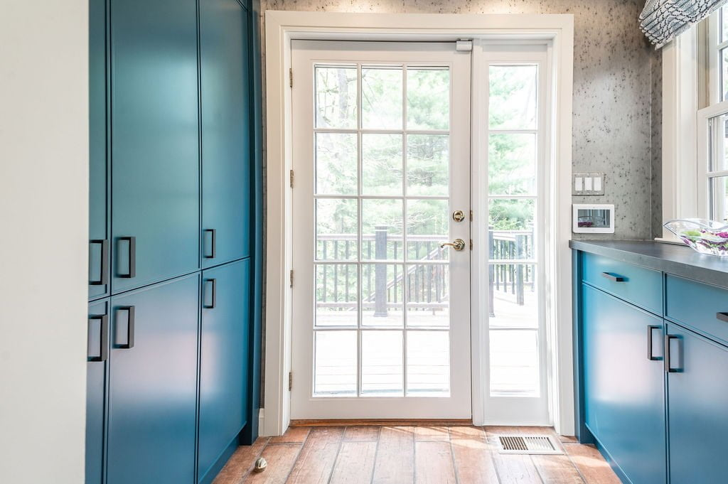 White door porch exit with transitional blue cabinetry, brown terra-cotta tile flooring and grey speckled walls