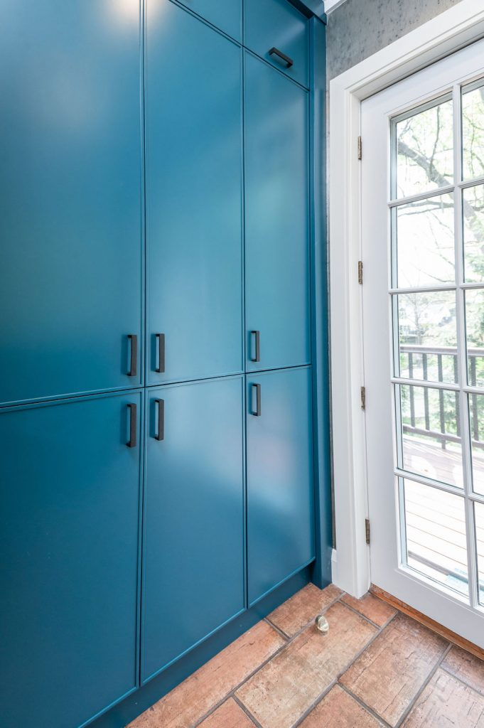 Transitional blue clothing storage cabinetry with brown terra-cotta tile flooring