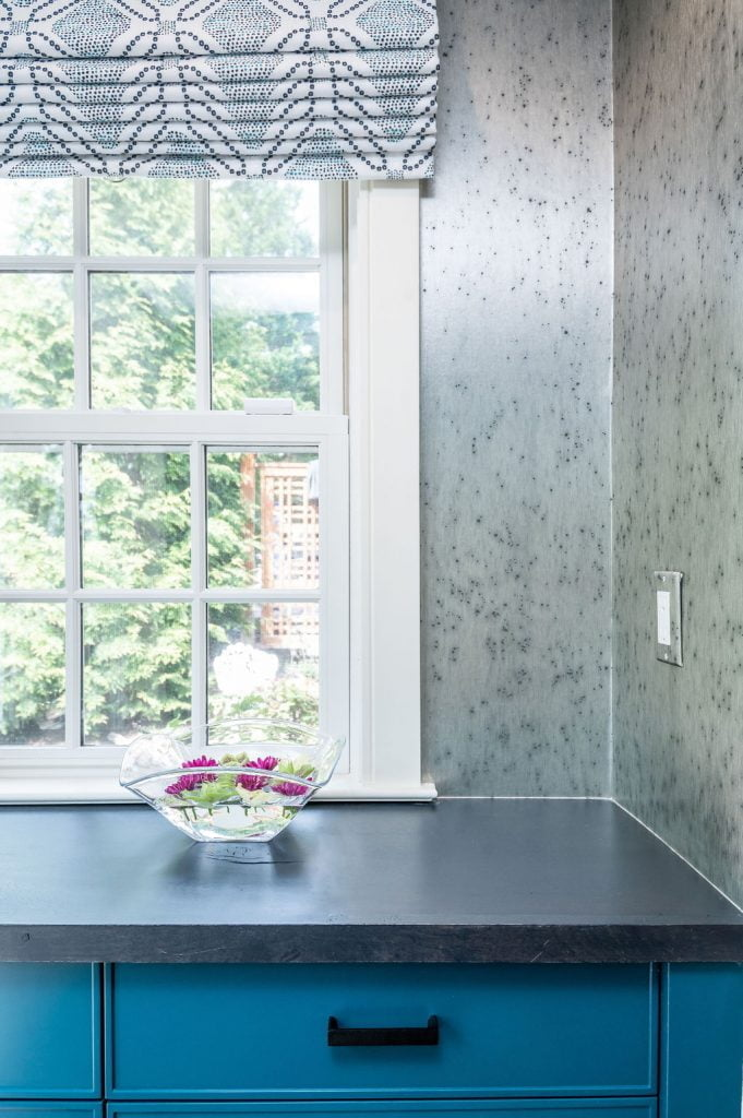 Transitional blue kitchen drawers with dark marble countertop and grey speckled backsplash