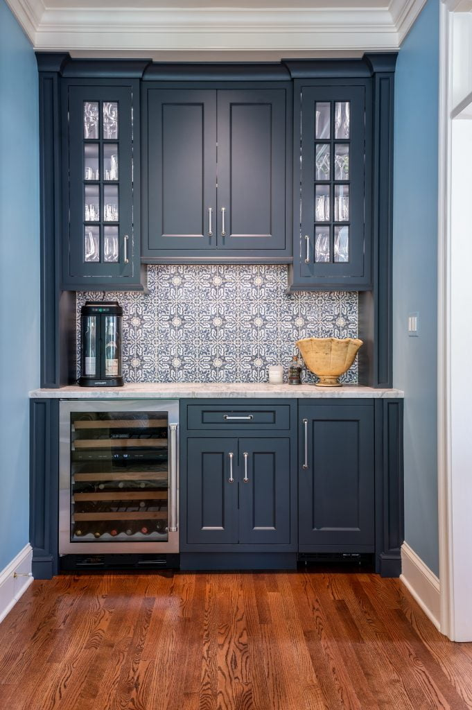 Transitional minibar with custom navy cabinetry, patterned tile backsplash and marble countertop
