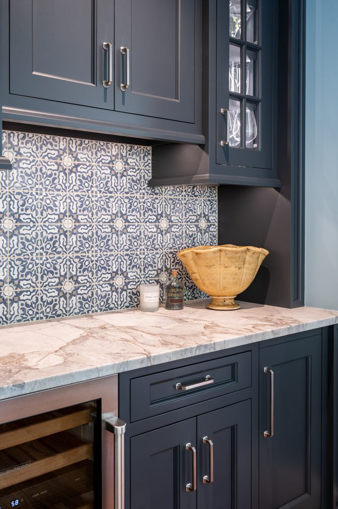 Custom navy cabinetry with patterned tile backsplash and marble countertop, stainless steel handles