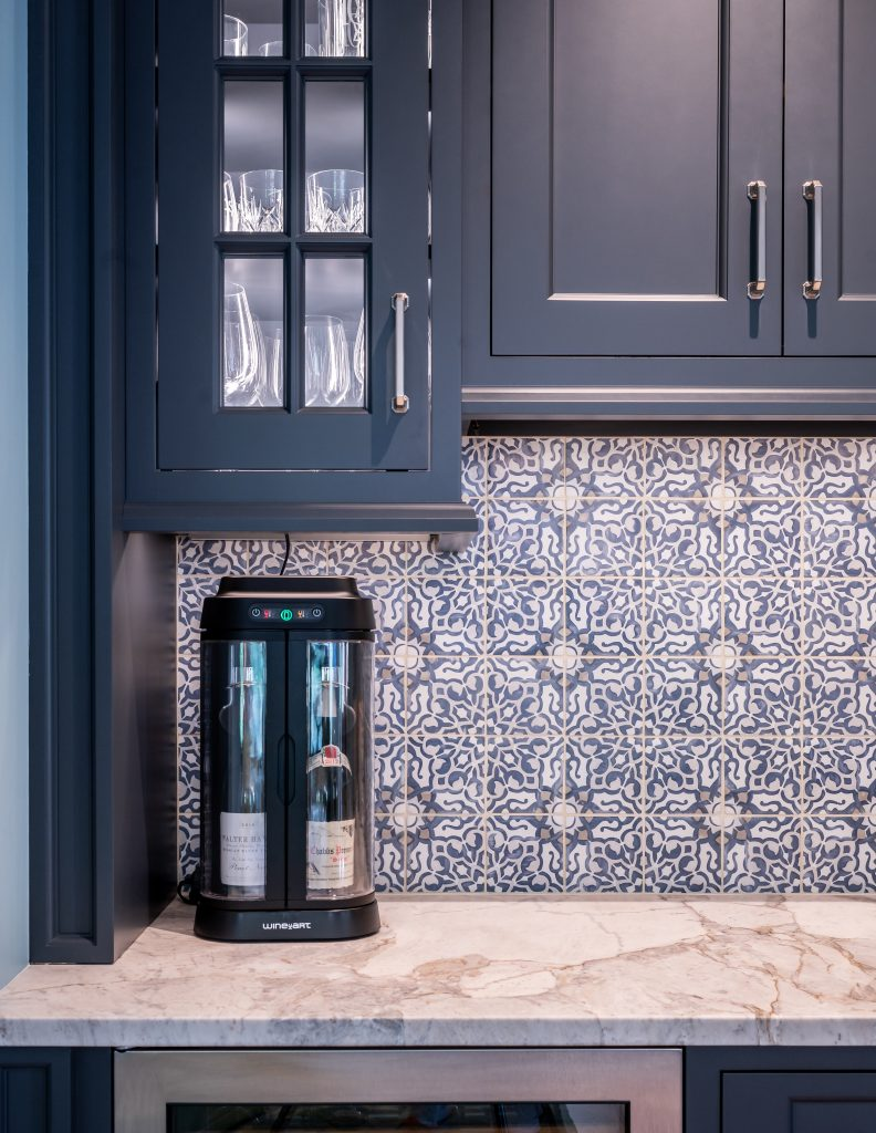 Custom navy cabinetry with patterned tile backsplash and marble countertop
