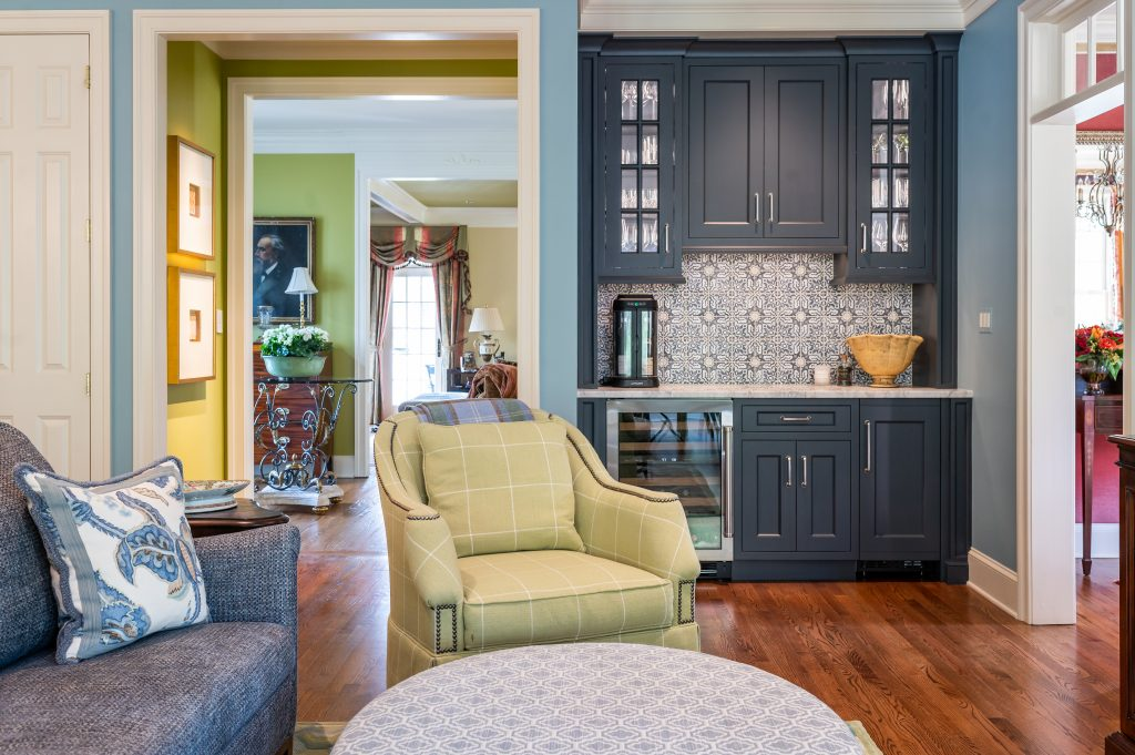 Transitional living room with custom navy cabinetry and decorative tile backsplash, with interior doorways