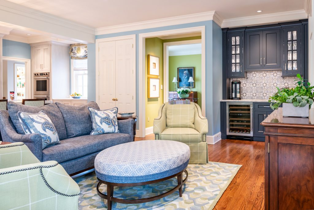 Colorful transitional family room with blue and green furniture and wall accents, and hardwood floor