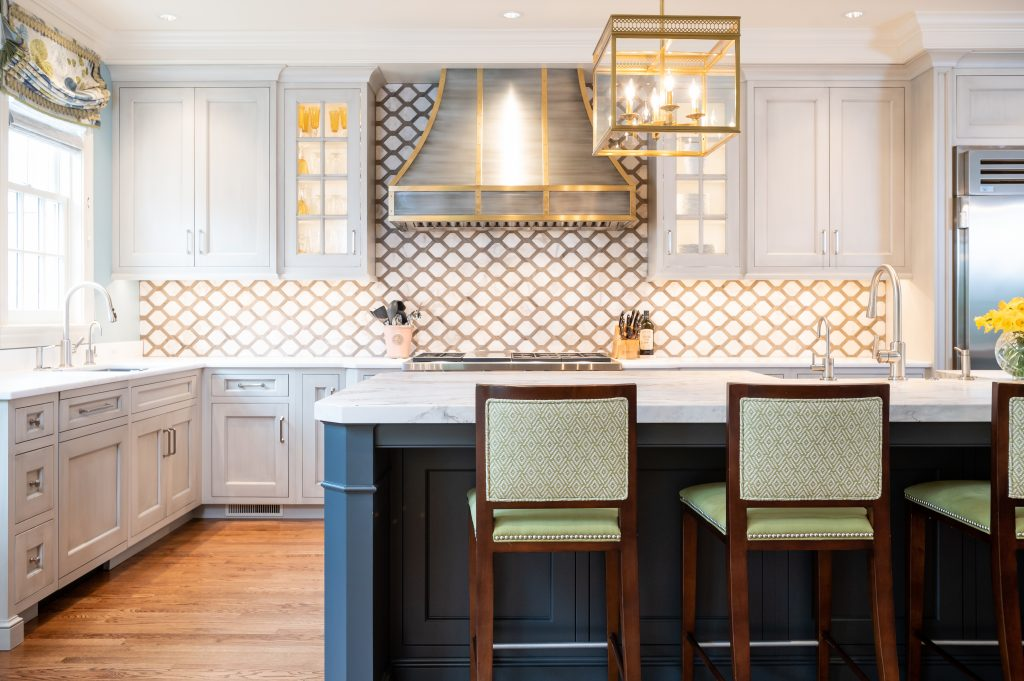 Transitional kitchen with custom cabinetry, hi-top chairs, and decorative tile backsplash with gold accent