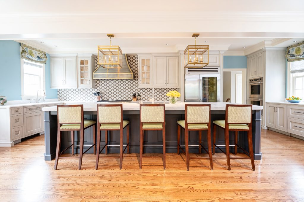 Transitional full kitchen with custom white cabinetry, five hi-top chairs, and blue and gold accents
