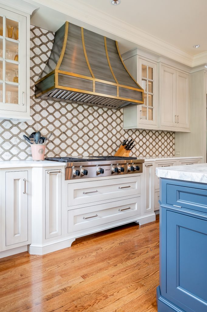 Transitional kitchen stovetop with white custom cabinetry and decorative hood vent
