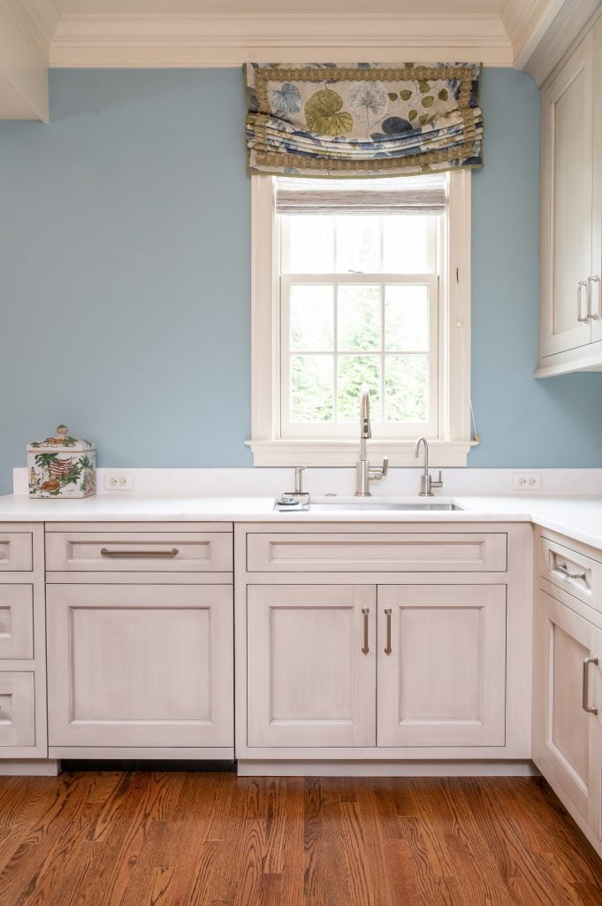 Transitional kitchen sink with white custom cabinetry and blue accent