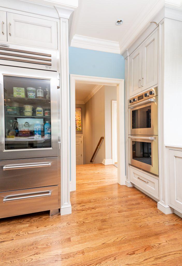 Hardwood floor kitchen with interior doorway and blue accent