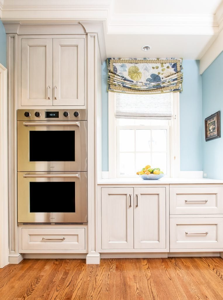 Transitional kitchen cabinets and drawers with stacked ovens and blue accent