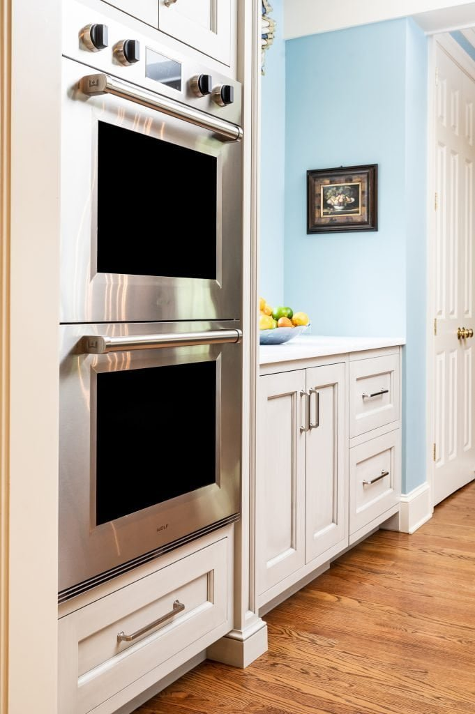 Two stacked ovens built into a transitional kitchen