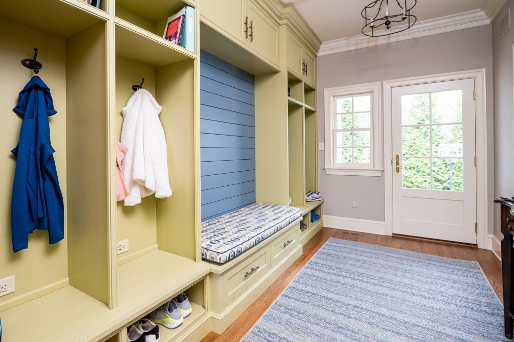 Transitional yellow mudroom cubbies with blue backsplash bench and exterior door