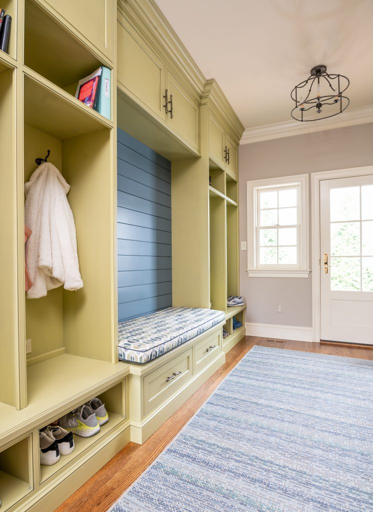 Transitional mudroom with cubbies, hardwood floor and blue rug
