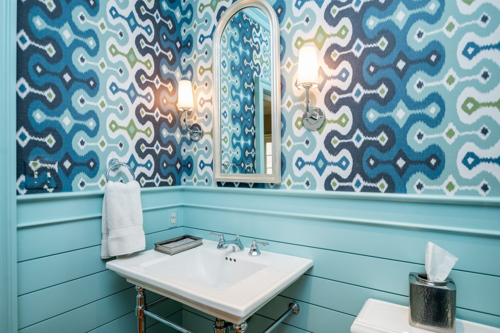 Transitional bathroom with blue wall molding, patterned blue wallpaper, and minimalist white sink