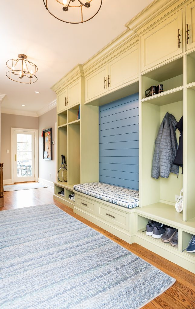 Transitional mudroom with yellow cubbies, blue bench, backsplash and rug