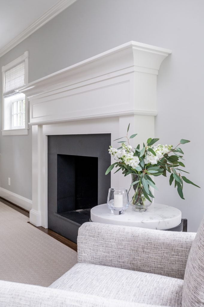Transitional white crown molding above dark grey fireplace, with light grey walls and light grey rug
