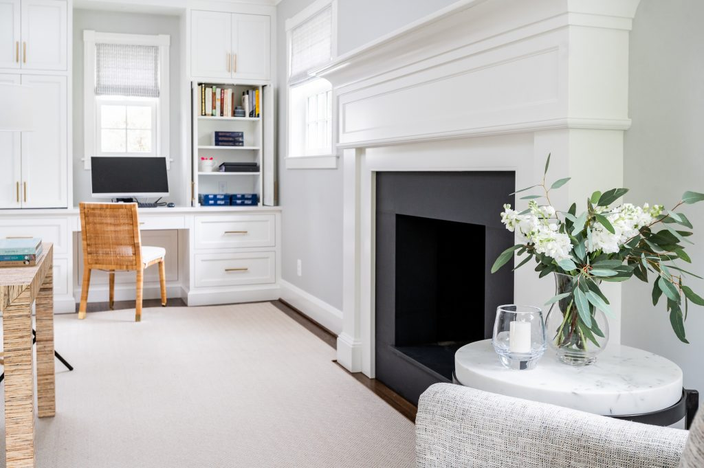 Transitional white cabinetry with woven wicker office chair, light grey walls, dark grey fireplace, and dark hardwood floor with light grey rug