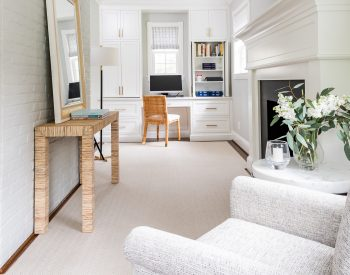 Transitional white cabinetry with woven wicker office chair in front of computer, light grey armchair, and dark hardwood floor with light grey rug (Entire room) (Zoomed in)