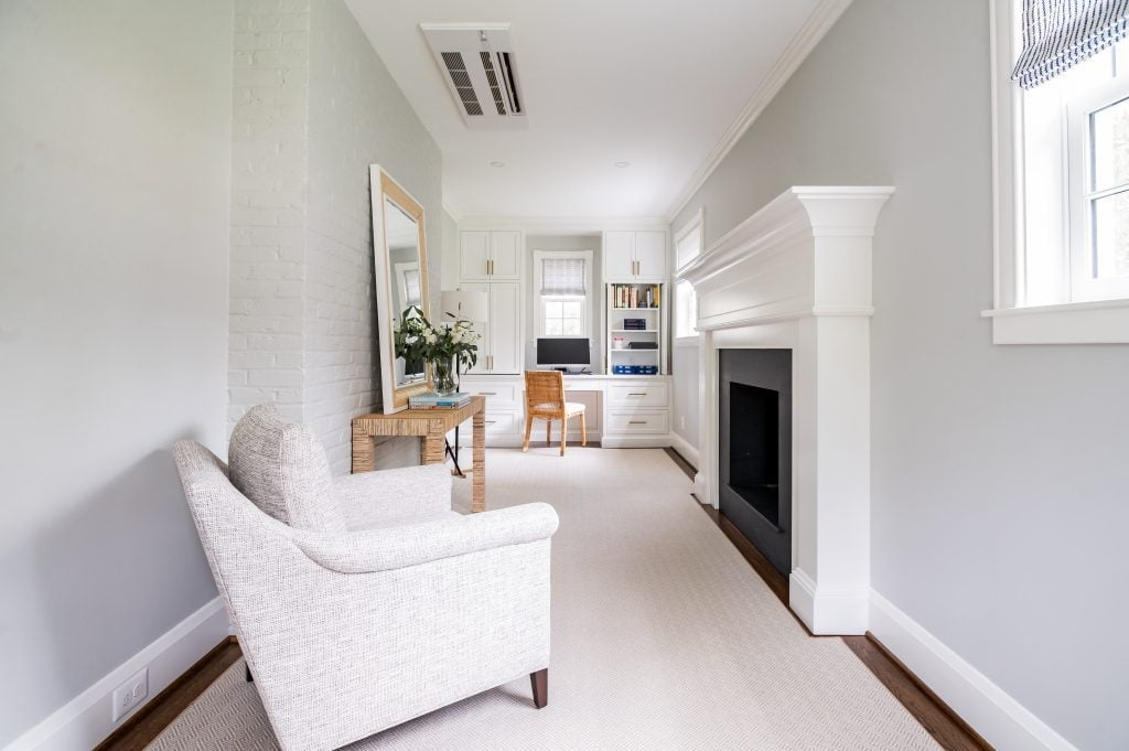 Transitional white cabinetry with woven wicker office chair in front of computer, light grey armchair, and dark hardwood floor with light grey rug (Entire room) (Zoomed fully out)