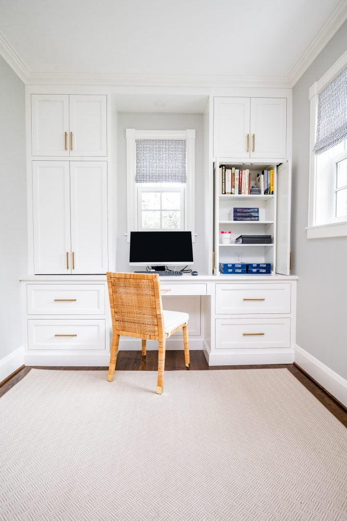 Transitional white cabinetry with woven wicker office chair in front of computer, and dark hardwood floor with light grey rug (Whole room) (Zoomed out) (Cabinet open)