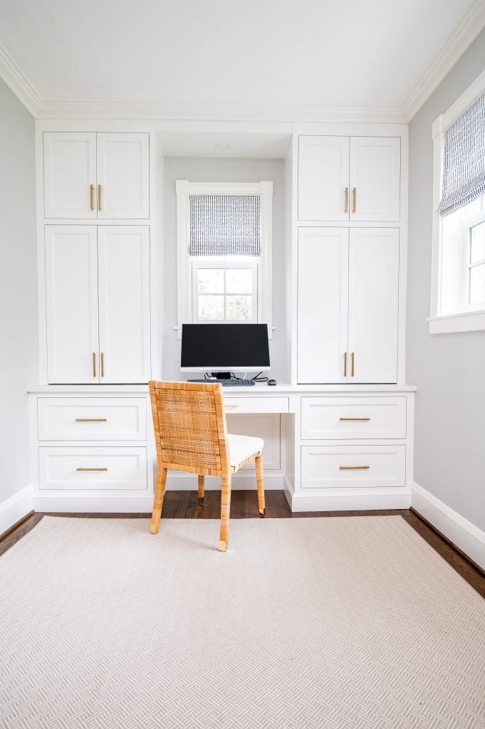 Transitional white cabinetry with woven wicker office chair in front of computer, and dark hardwood floor with light grey rug (Whole room) (Zoomed out)