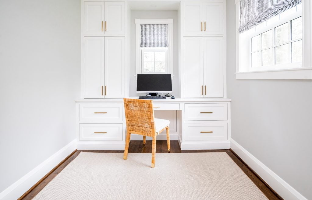 Transitional white cabinetry with woven wicker office chair in front of computer, and dark hardwood floor with light grey rug (Whole room) (Cabinet closed)