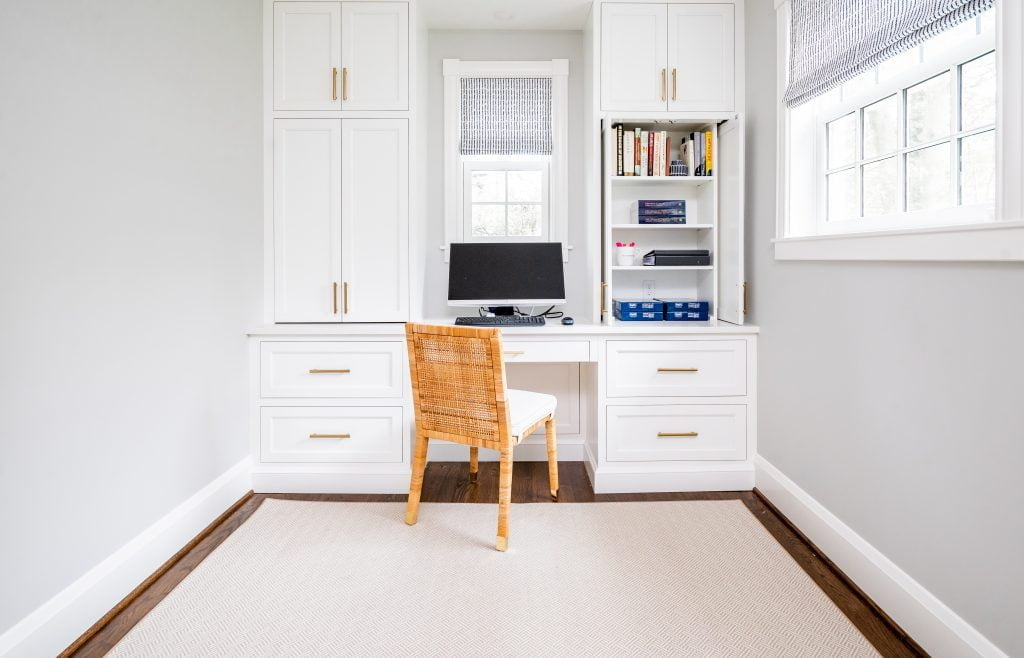 Transitional white cabinetry with woven wicker office chair in front of computer, and dark hardwood floor with light grey rug (Whole room)