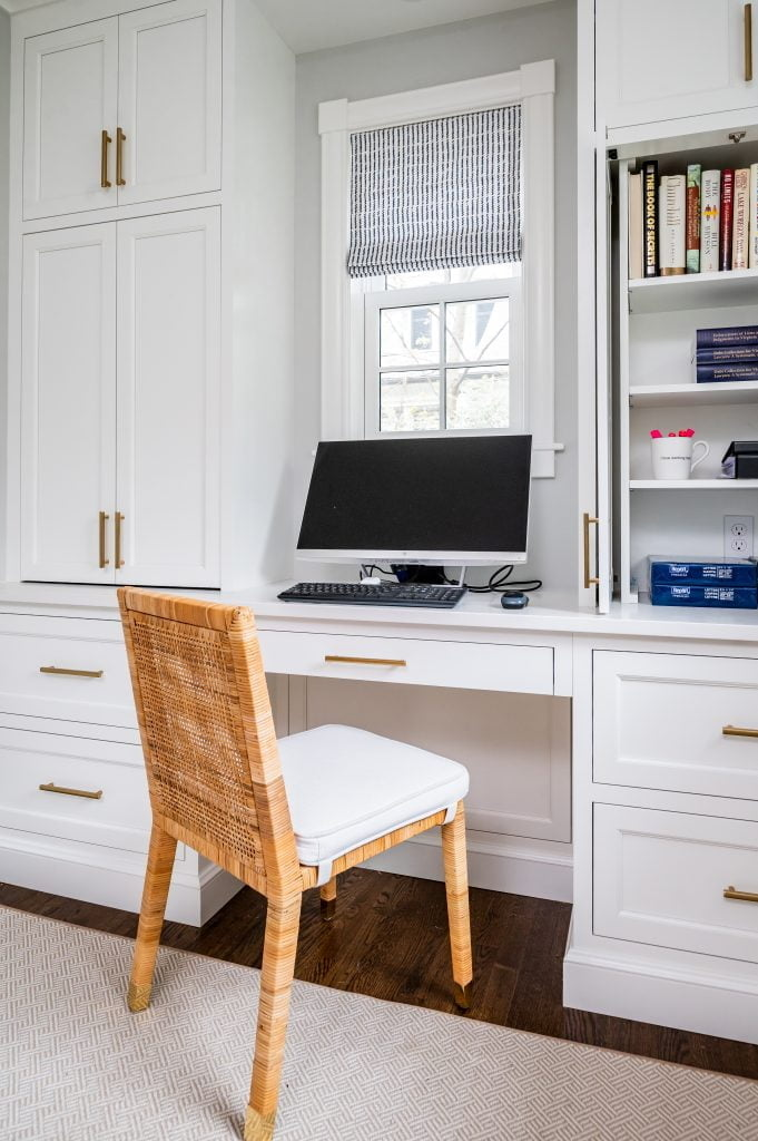 Transitional white cabinetry with woven wicker office chair in front of computer (Zoomed out)