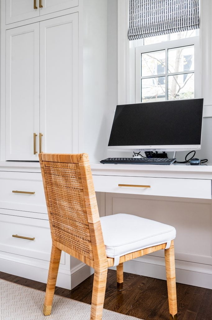Transitional white cabinetry with woven wicker office chair in front of computer