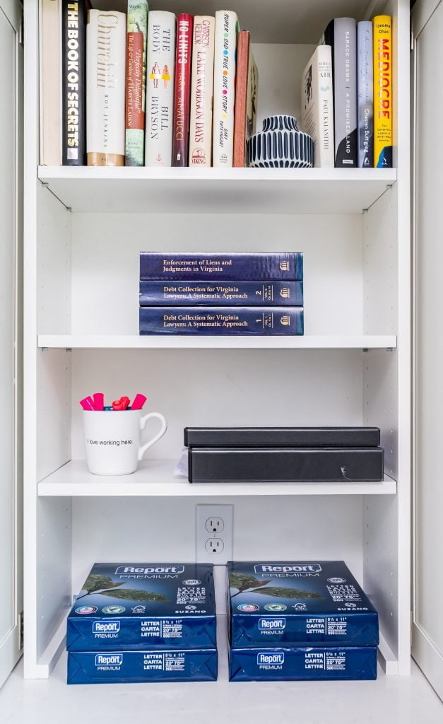 White shelving unit with books and binders and pens