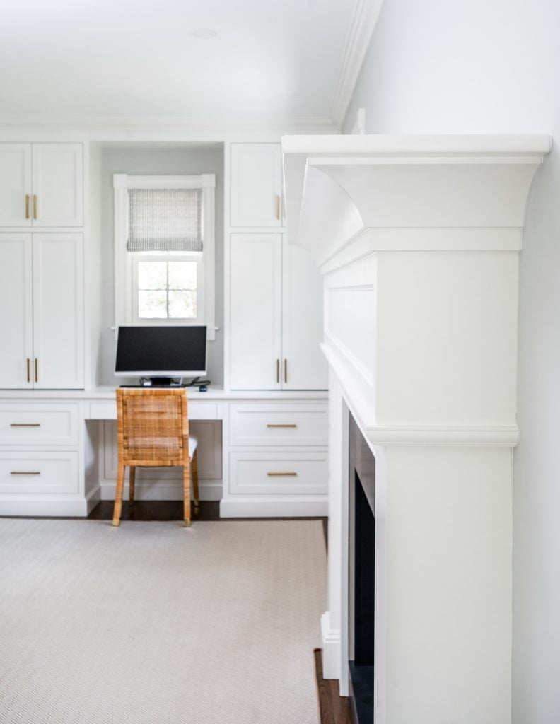 Transitional white crown molding above fireplace, with light grey walls and light grey rug