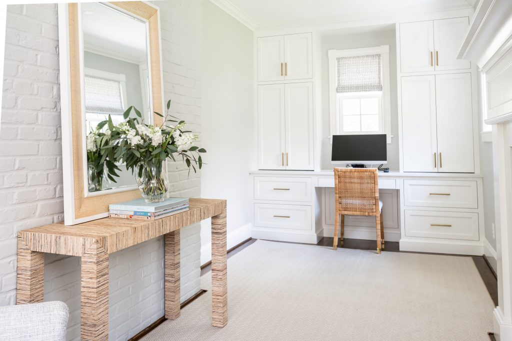 Transitional white cabinetry with woven wicker office chair in front of computer, and dark hardwood floor with light grey rug (Different angle)