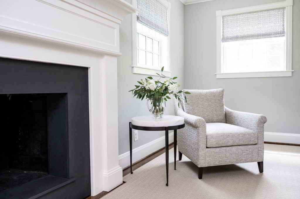Transitional white crown molding above dark grey fireplace with light grey walls and light grey armchair and white marble side table