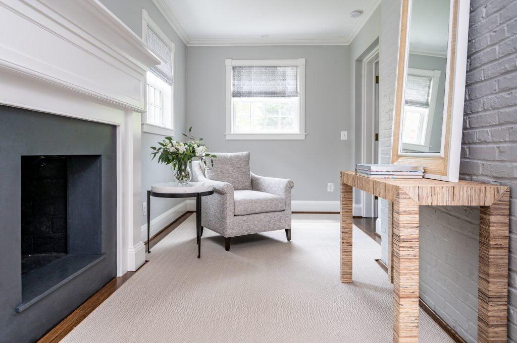 Light grey armchair with dark hardwood flooring and light grey rug, and light grey walls (Zoomed out)