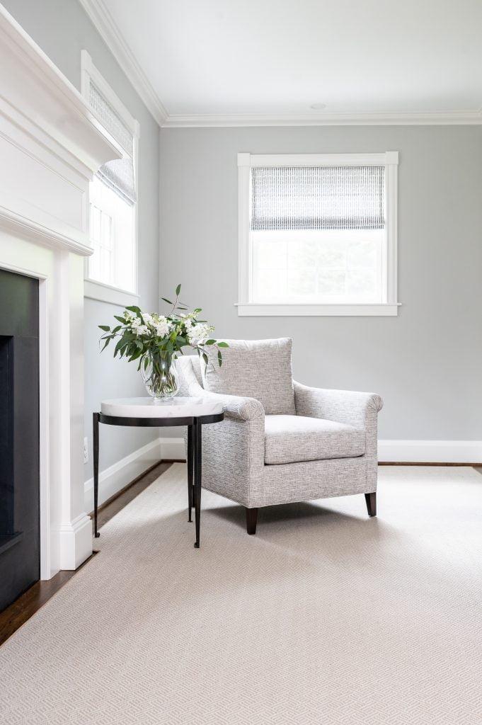 Light grey armchair with dark hardwood flooring and light grey rug, and light grey walls