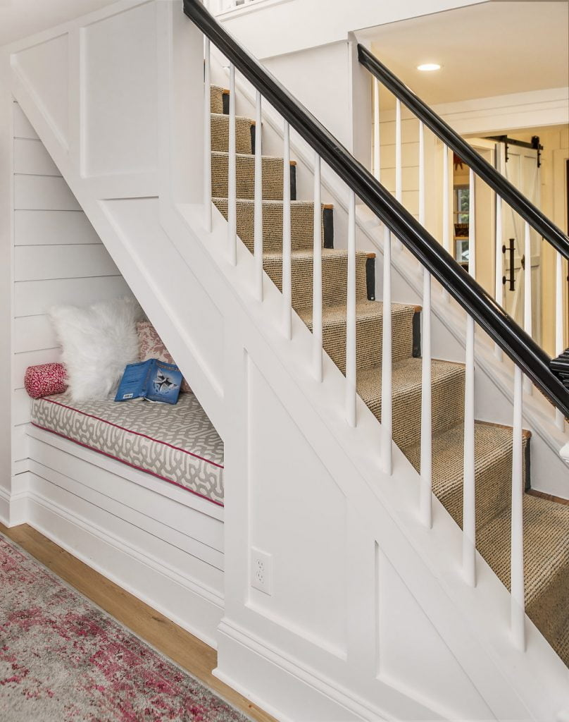 Interior staircase with beige carpet, black and white wooden railings, and white paneling on wall, and sitting nook