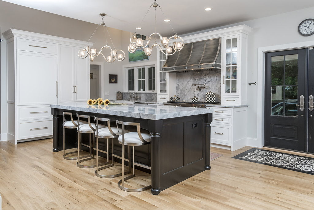 Transitional style kitchen and dark hardwood island with custom white cabinetry, granite countertops, and steel hi-top chairs
