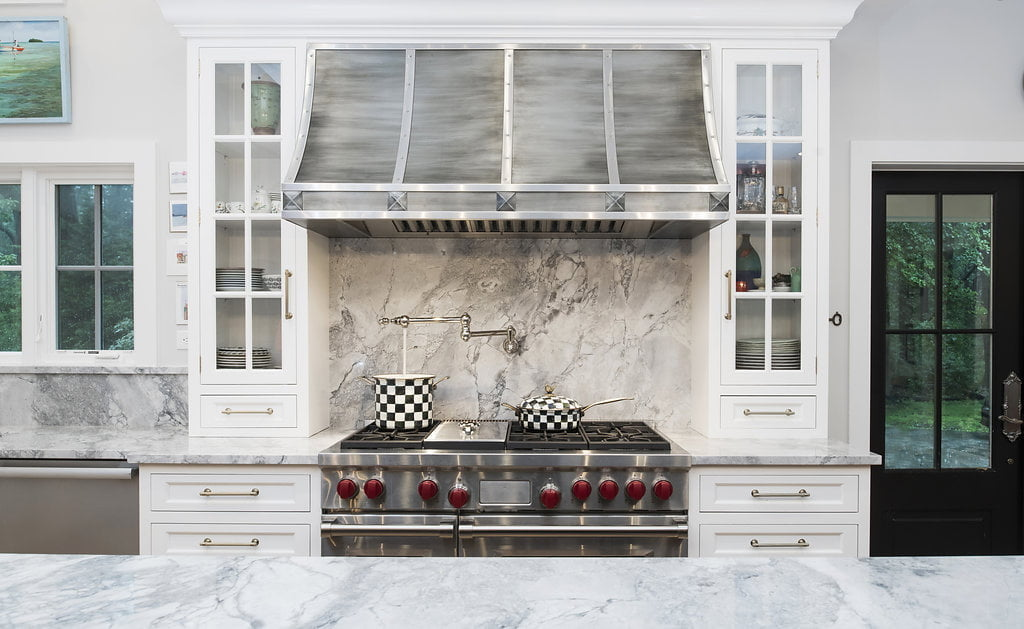 Transitional stainless steel stovetop kitchen with custom white cabinetry, granite countertop and backsplash, and transitional style hood vent