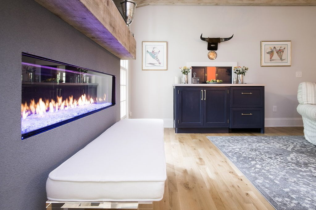 Inset electronic fireplace with white cushioned bench and rustic wooden ledge