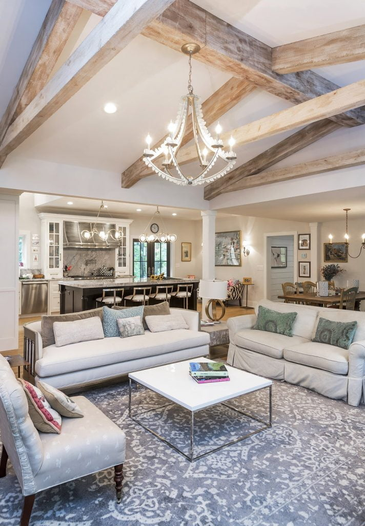Transitional/Rustic beige family room with exposed wooden beams and decorative chandelier