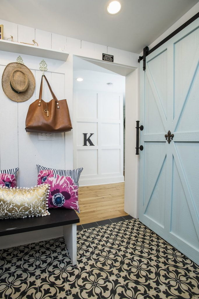 Interior doorway with white paneling on walls and light blue sliding barn door