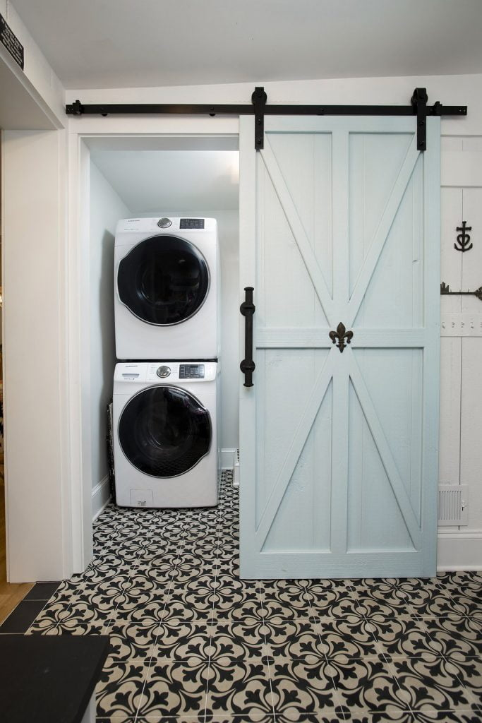 Light blue sliding barn-door-style door into laundry room with black and white patterned carpet