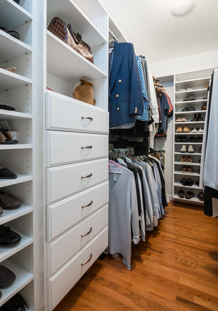 Wall-in closet with white cabinetry and medium hardwood flooring
